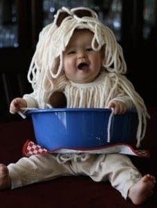 A baby in a Halloween costume made to look like a bowl of spaghetti and meatballs